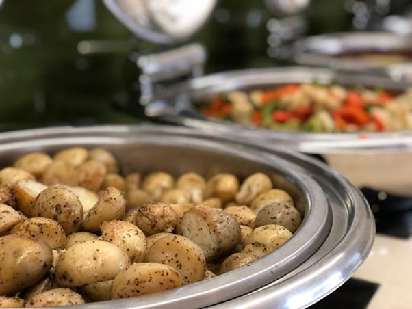 Hot roasted potatoes sprinkled with herbs and pepper sitting in dish