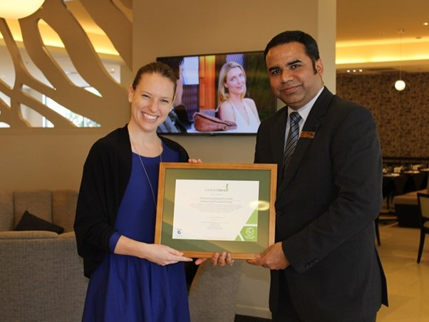 Two people smiling and holding a framed certificate.