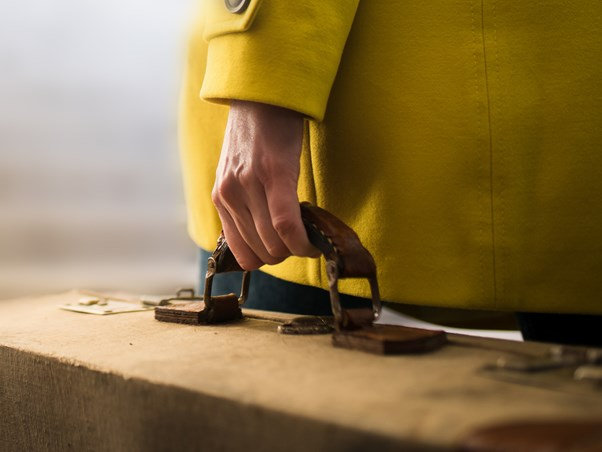 Close up of woman in yellow coat carrying a quality suitcase.