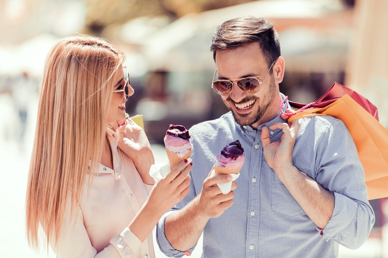 Couple wearing sunglasses, eating ice cream and holding shopping bags.