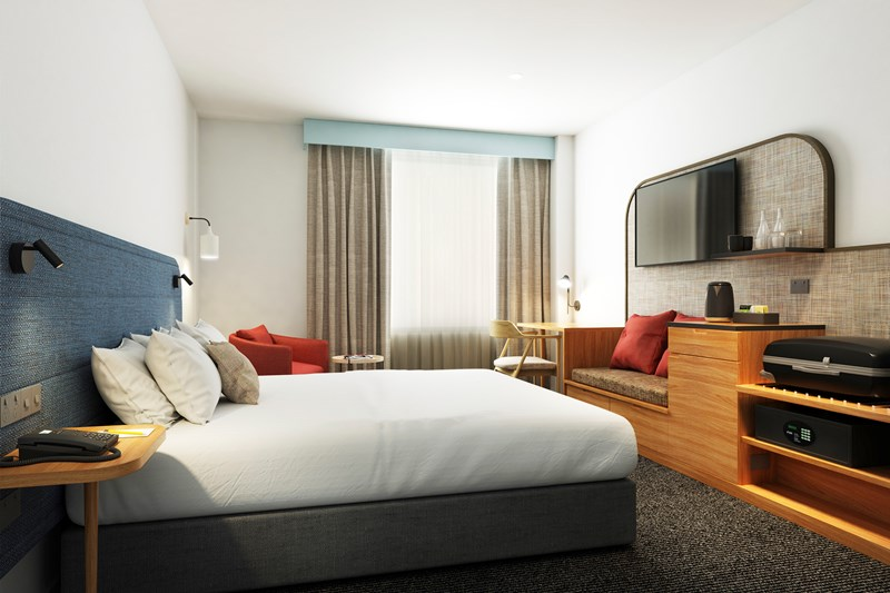 View of one bed, lounge seat, flatscreen, bedside table and large windows.